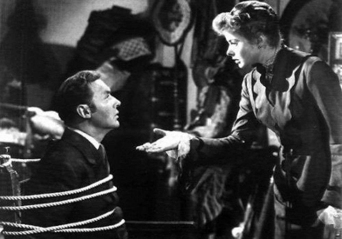Ingrid Berman talks to a tied up Charles Boyer