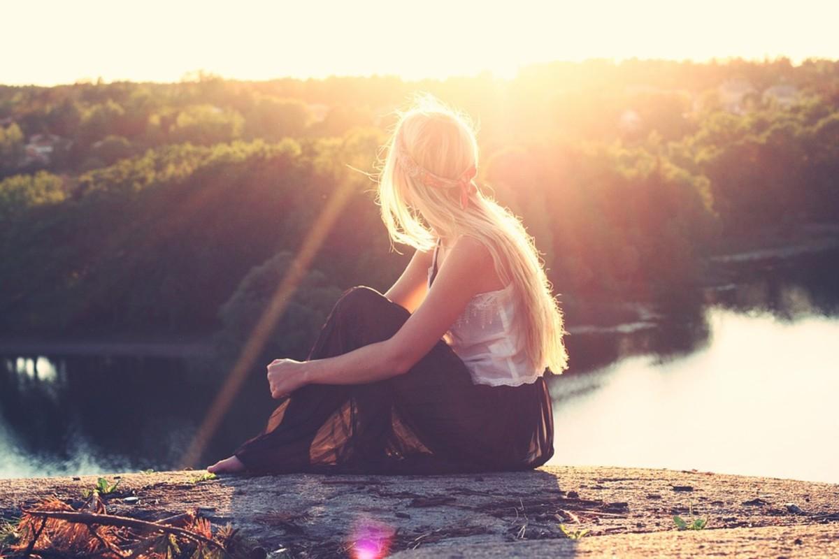 Woman sitting by waterside