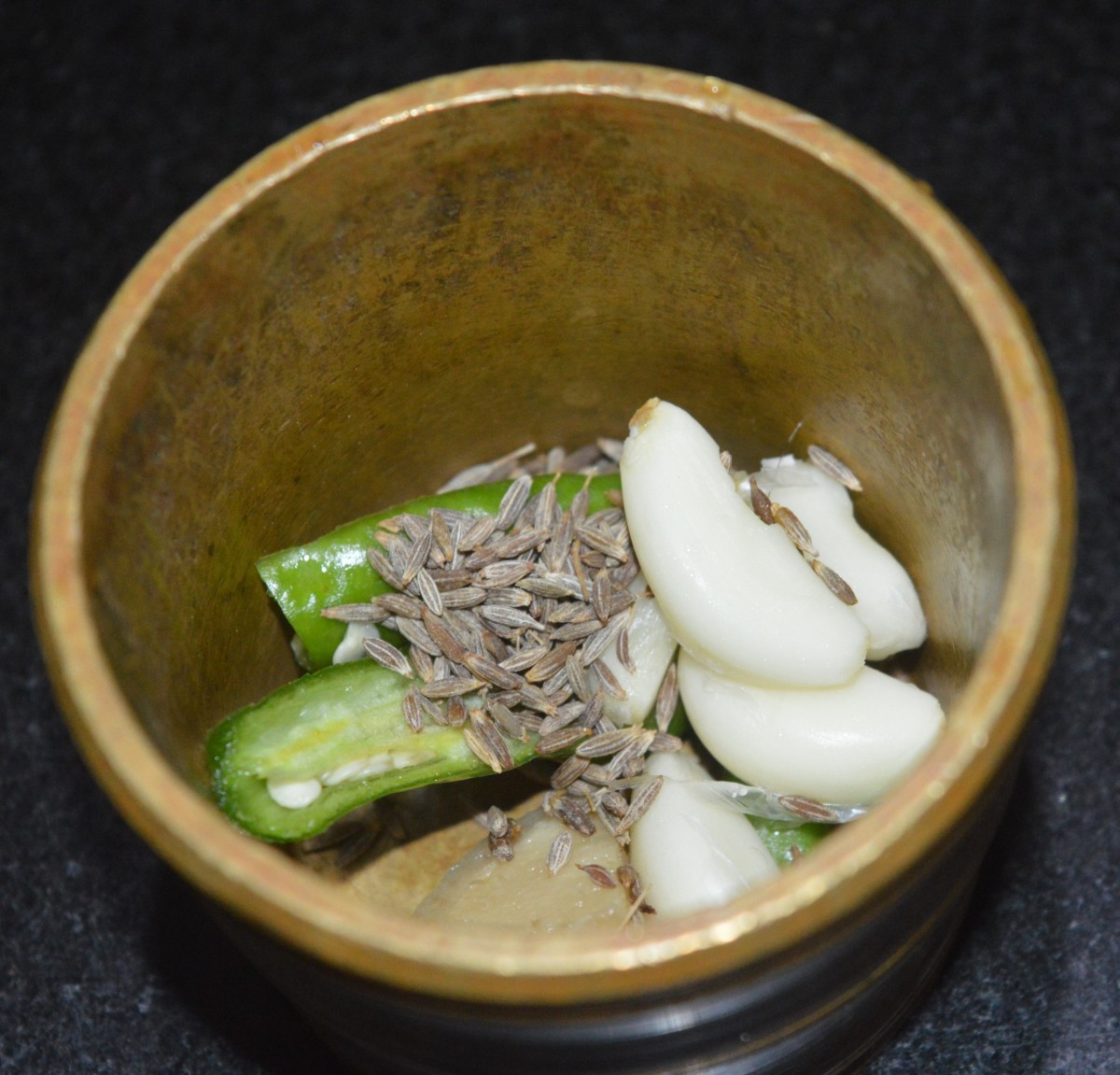 Step two: Add garlic cloves, cumin, ginger, and green chilies to a mortar and pestle. Make a coarse paste.
