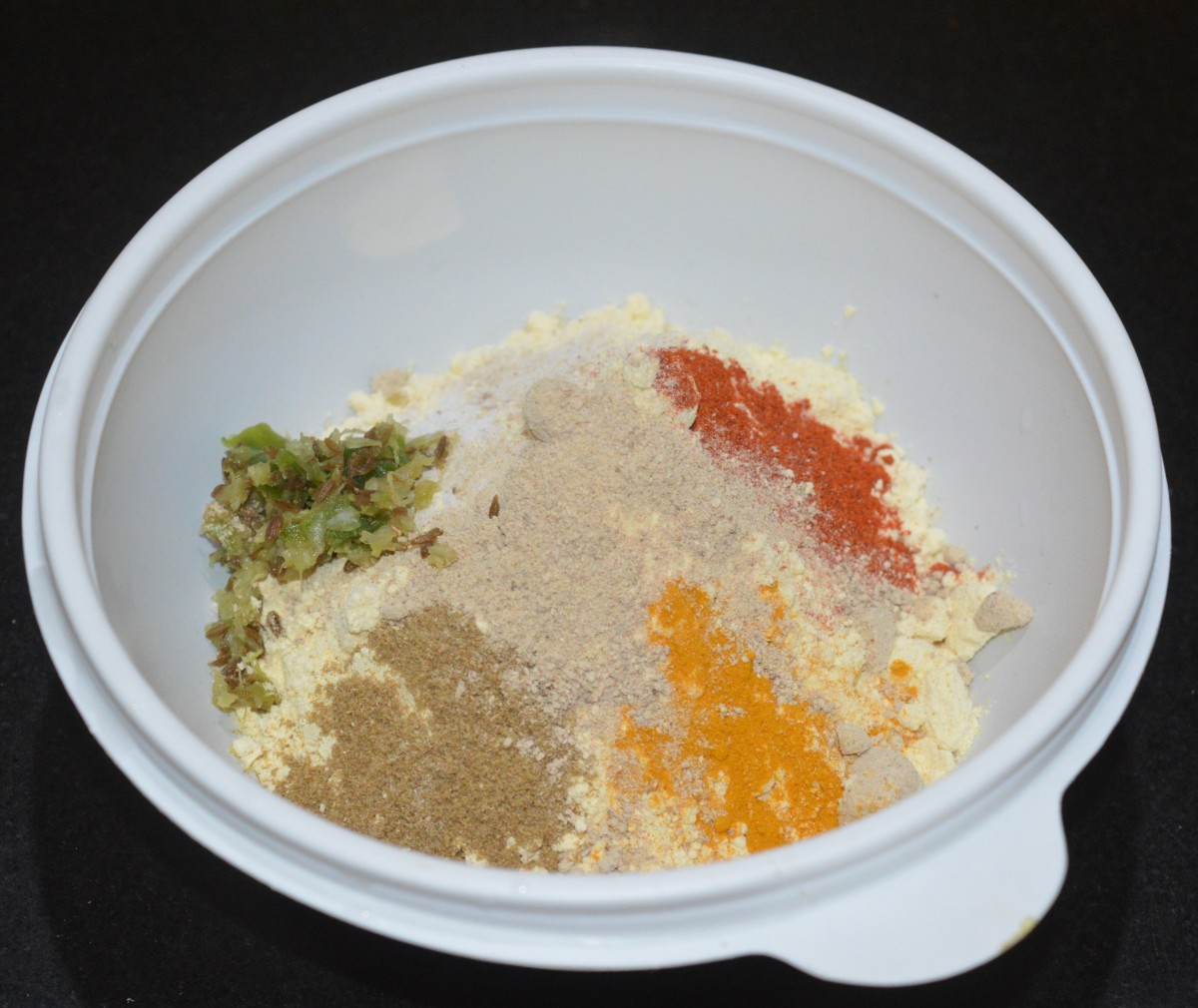 Step three: For making the batter, add chickpea flour (besan), red chili powder, the paste, amchur powder, coriander powder, turmeric powder, and salt to a mixing bowl. Add water little by little and make a lump-free thick batter.