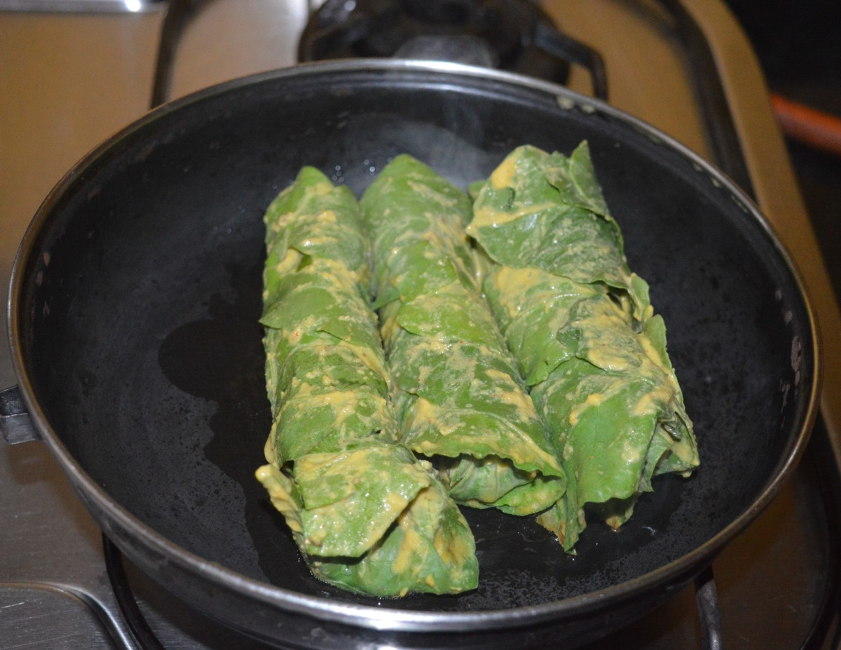 Step seven: Shallow-fry the rolls. Heat some oil in a pan. Place the spinach rolls on it. Keep the heat at medium-low. Cook the rolls by turning them often to ensure uniform cooking all over.