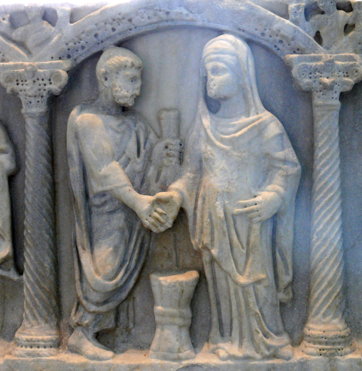 A Roman couple joining hands. The bride's belt tied in a knot symbolized the husband's unification with her.
