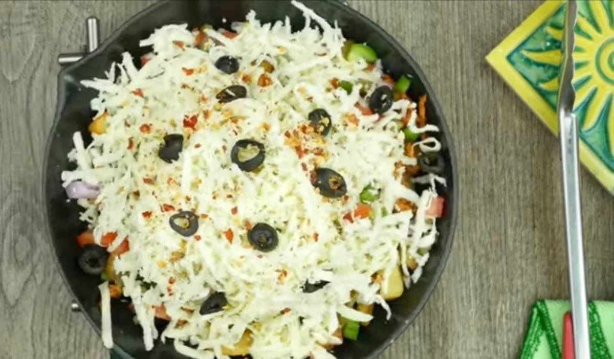 Layer it with more cheese and chopped black olives. Sprinkle some salt, red chilli powder and dried oregano.