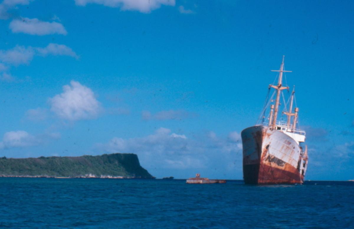 Old shipreck sitting tall on coral shelf at GabGab Beach