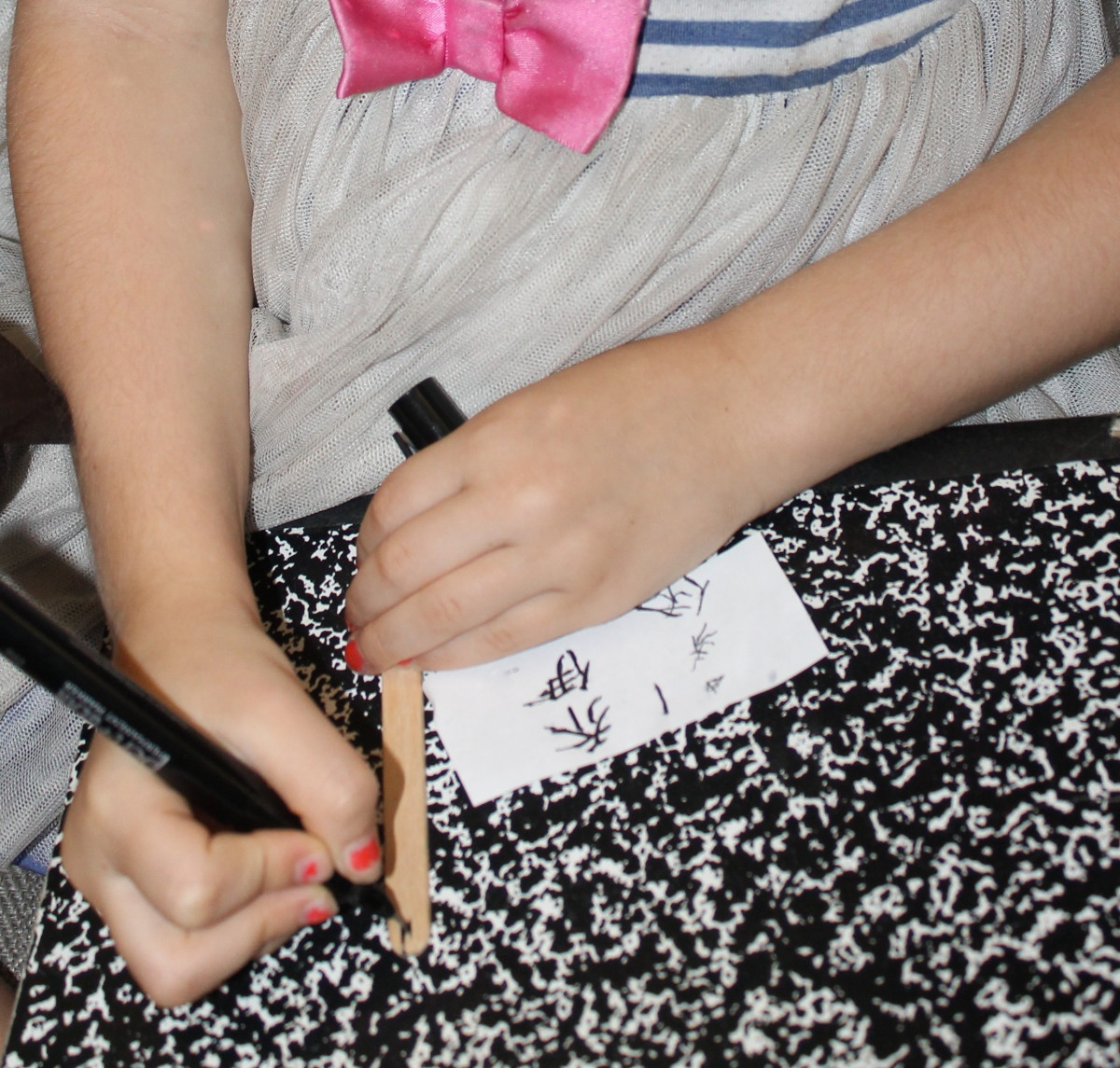 """Each child attempted to write their name in Chinese characters on their """"bamboo"""" slip made from a craft/popsicle stick."""