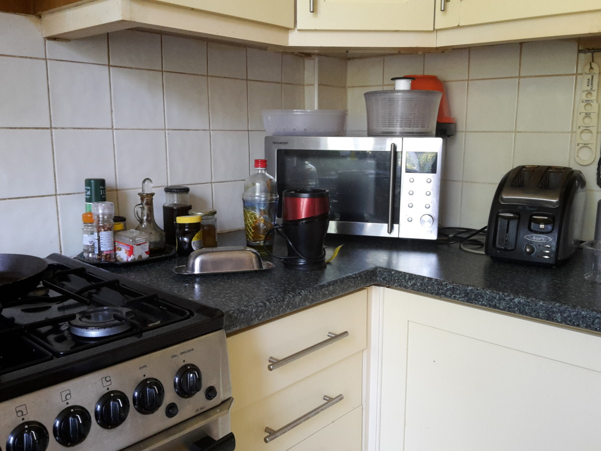A modern kitchen with microwave oven, juicer, toaster and salad shaker