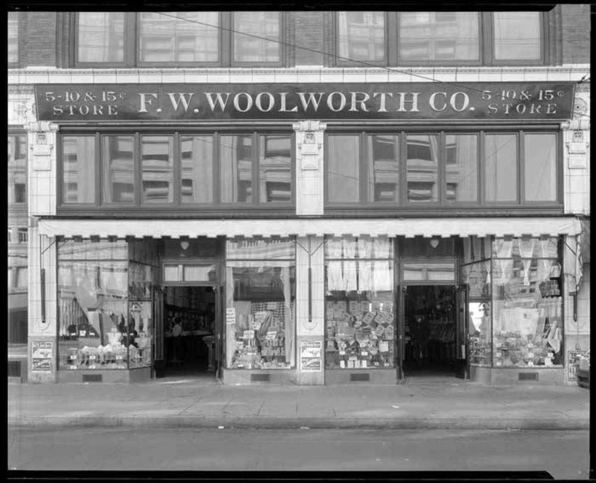 In this photo, Woolworth's windows are filled with boxes of soap powder, bolts of fabric, stacks of notebooks, rows of socks, and countless other things to lure customers inside.