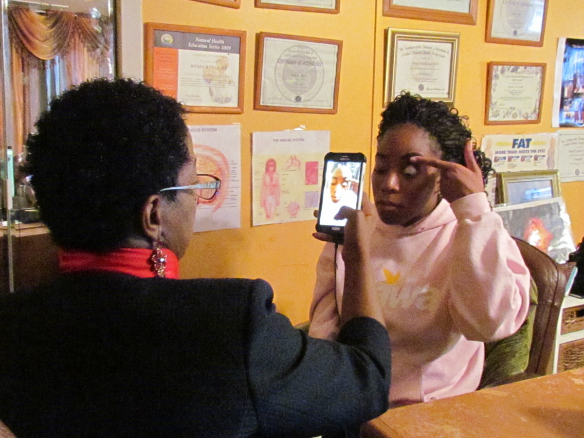 Wendy, is taking photos of another client's eyes as she assess the different health concerns that shows up withn the eyes.