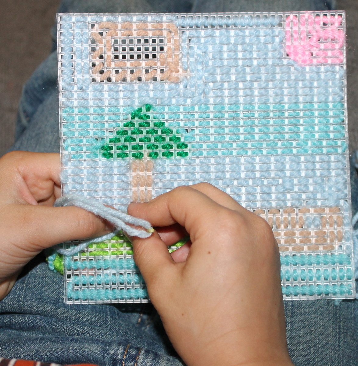 """Lower elementary aged child finishing up the simplified """"embroidery"""" project"""