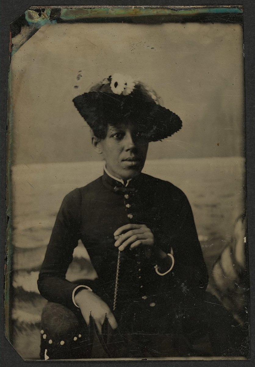 Woman in a straw hat with one side of brim turned up. Circa 1880s