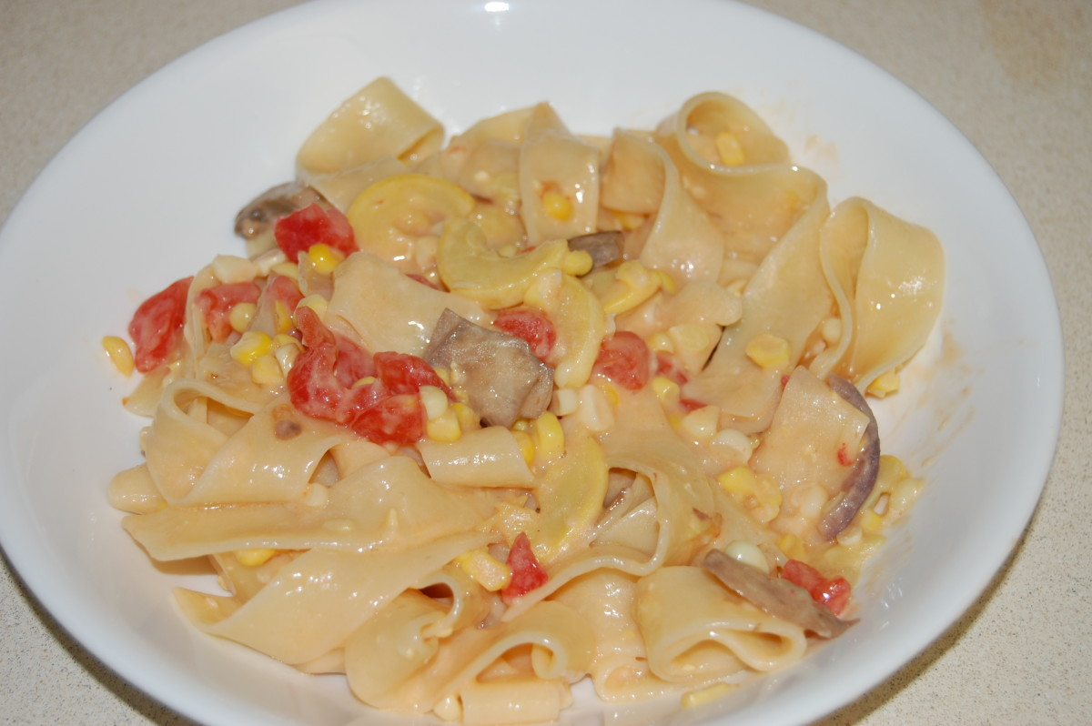 Pappardelle pasta in Alfredo, with mushrooms, fresh yellow squash, fresh tomato, and fresh corn