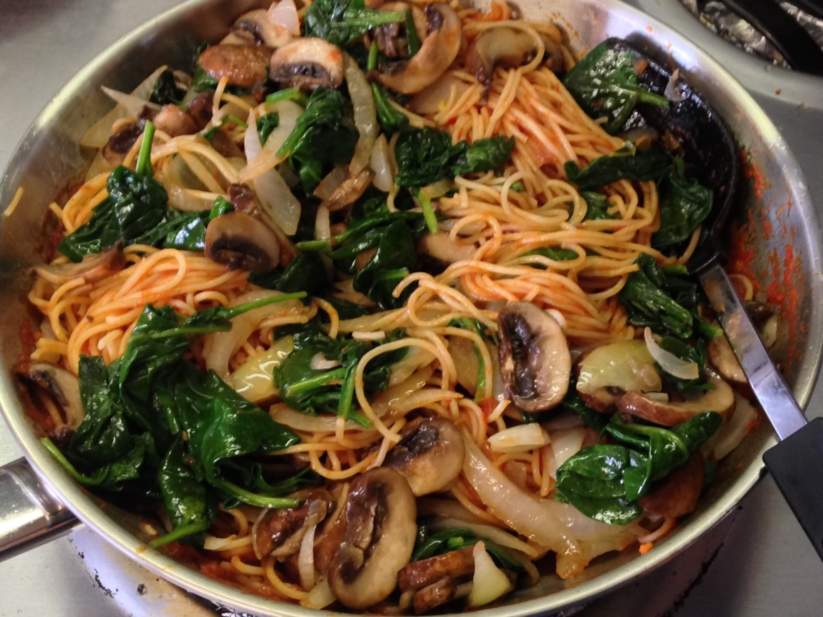 Skillet with vermicelli in Arrabbiata sauce with sauteed sweet onions, baby bella mushrooms, and baby spinach