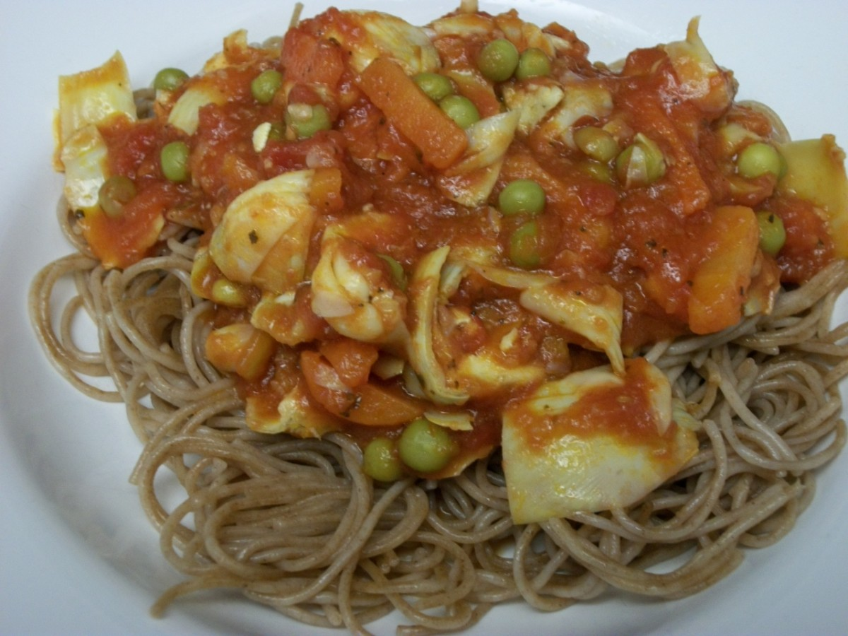 Spelt pasta in tomato and olive oil sauce with artichoke hearts, peas, and carrots