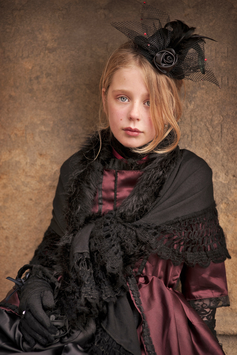 Portrait photograph of a young girl wearing Victorian-style clothing during an appearance at the Whitby Gothic Weekend festival.