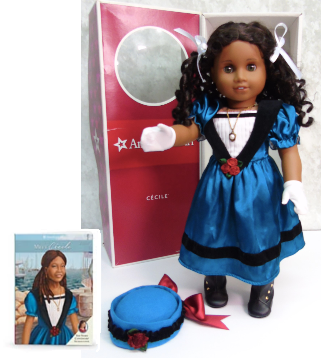 A Cécile Doll, posed with her accessories, packaging, and Meet Cécile book