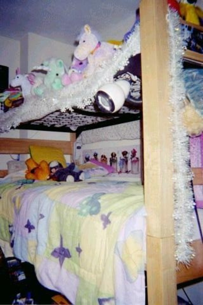 A loft bed with mattress on top of desk and the top bunk used as storage.