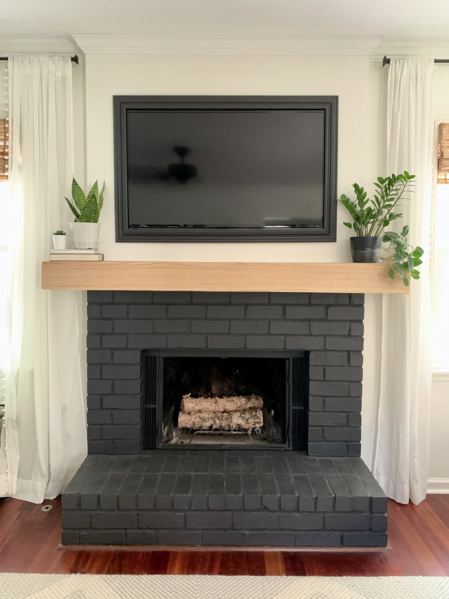 Black brick fireplace with white oak beam mantle.