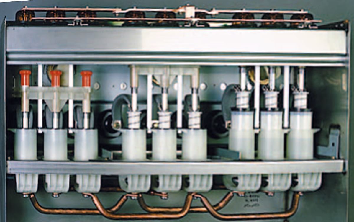 The Schneider Electric's RM6 RMU pictured from backside with covers removed. The main Common bus bar is visible exposed at the bottom, whereas the earth bus bar is at the top.