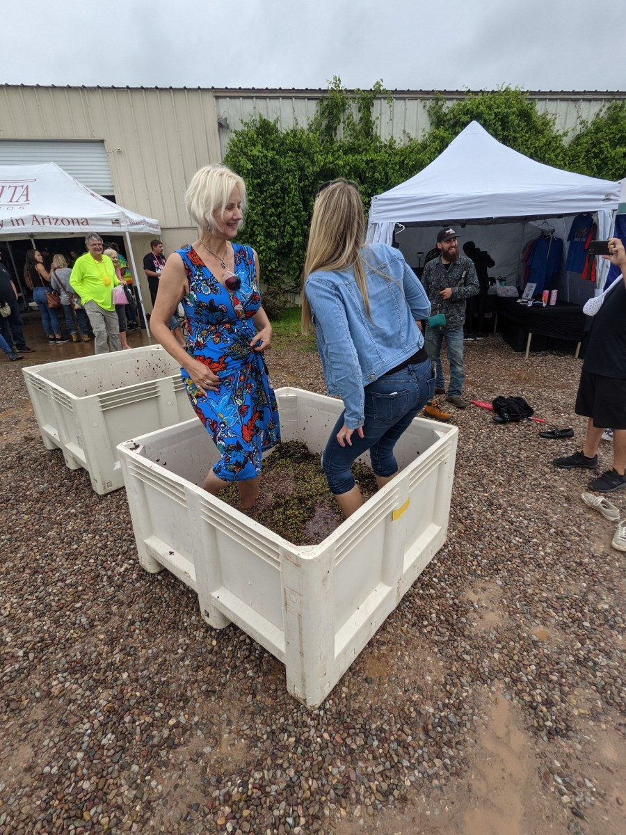 My wife and another visitor stomping grapes at July 2021 Festival