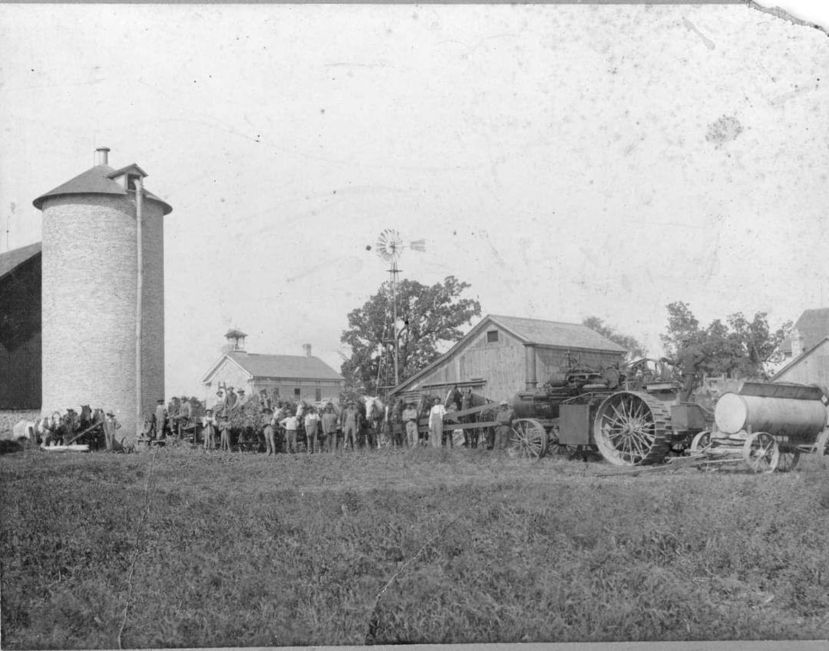 The Honey Creek Stone White School is between the silo and windmill in the distance. You can see the second floor.  This picture was taken around 1900.