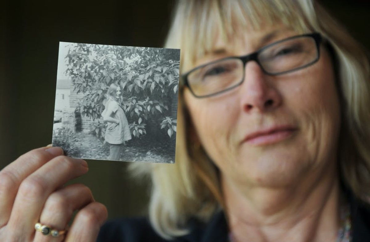 At 18, Australian women, Linda Miles was forced to give up her child for adoption. She is holding a picture of when she was pregnant.