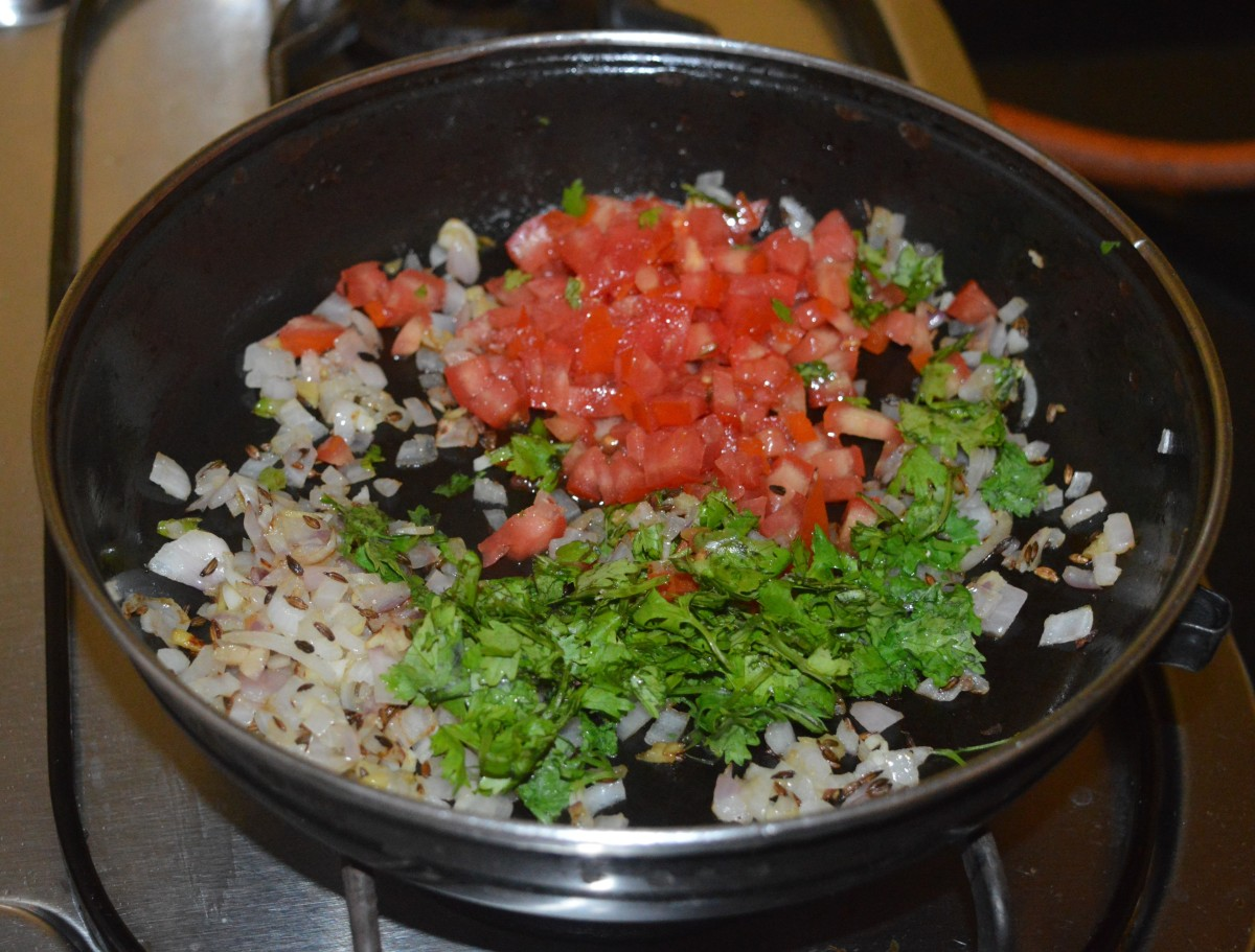 Add chopped tomatoes, coriander leaves, and some salt. Adding salt quickens the cooking process.
