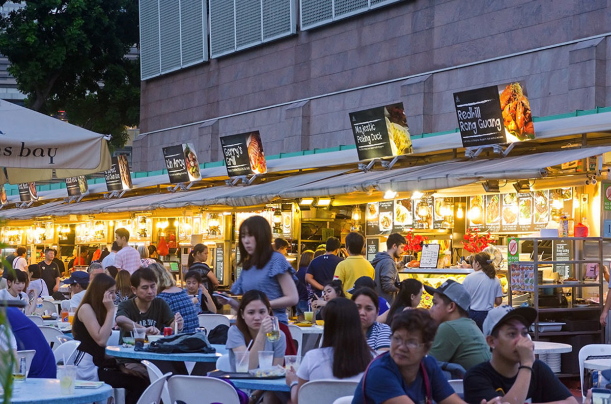 An open-air Singaporean eatery during early evening.