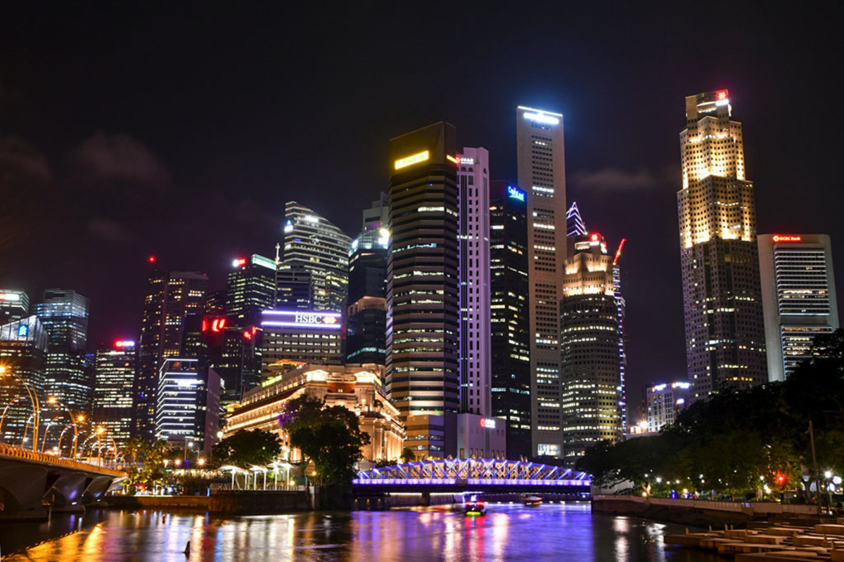 The Singapore River at night and the many skyscrapers beside it.