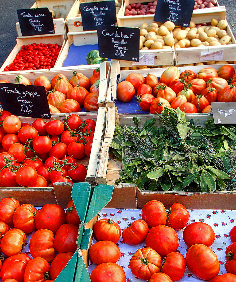 Heirloom tomatoes and fresh herbs for sale at a farmer's market.
