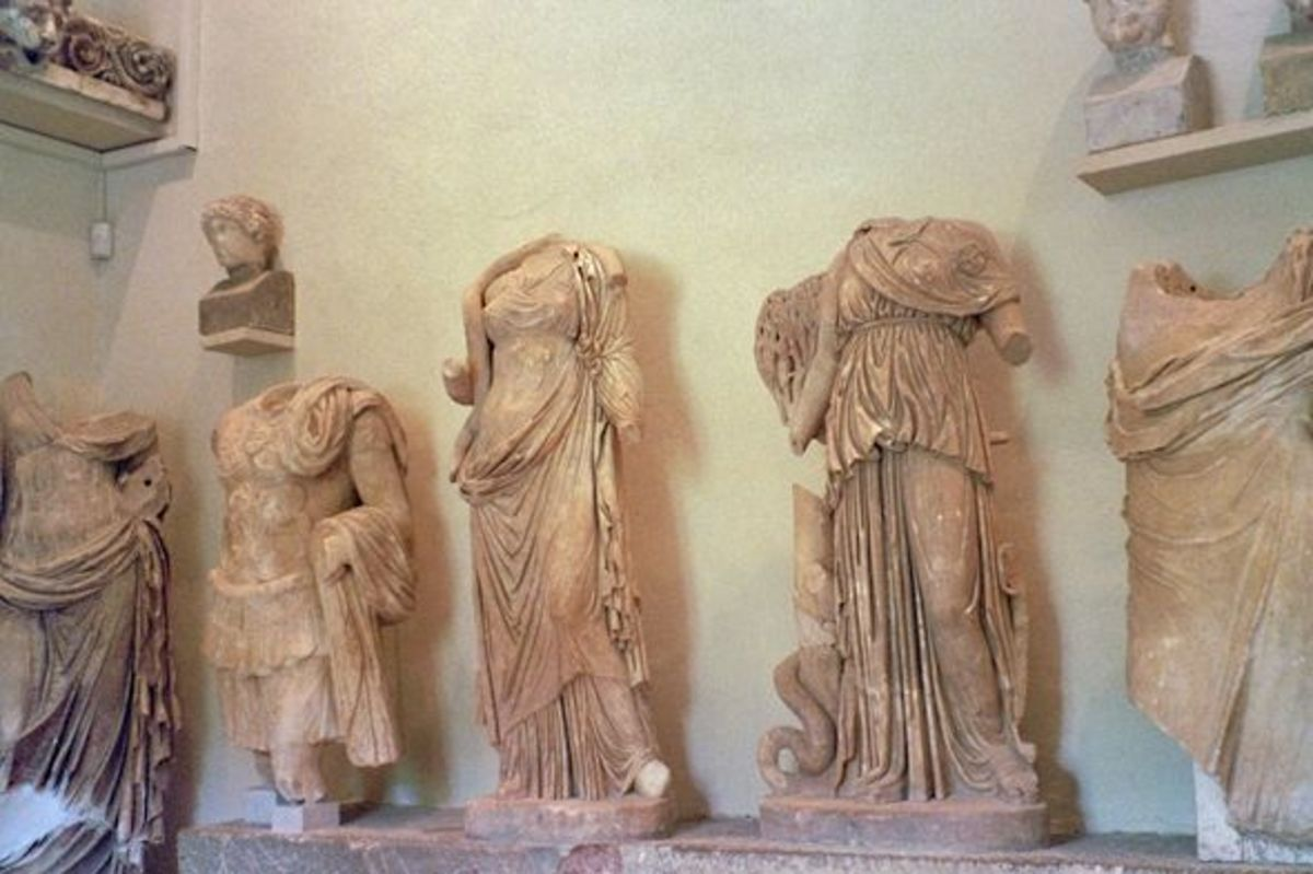More statues. I'm not sure about the lefthand figure -- possibly a Roman portrait of Asclepius, armed? -- but in the middle is another Hygeia, goddess of health. It's a pity she and the Athena at right (with a serpent around an olive tree) have lost
