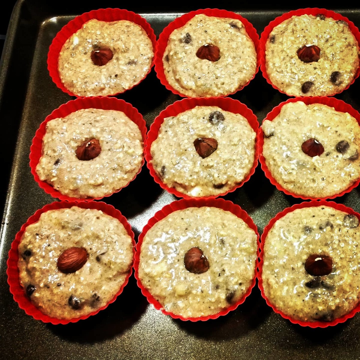 Spoon muffin dough into each silicon baking cup and place a hazelnut on top.