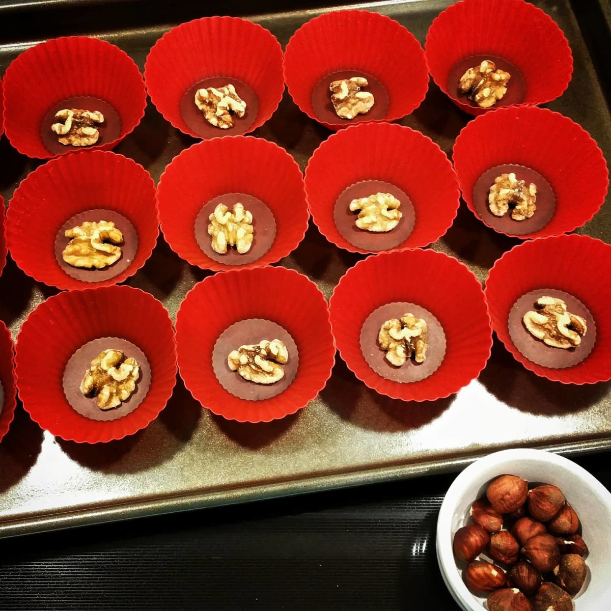 Set a half walnut into the bottom of each silicone baking cup.