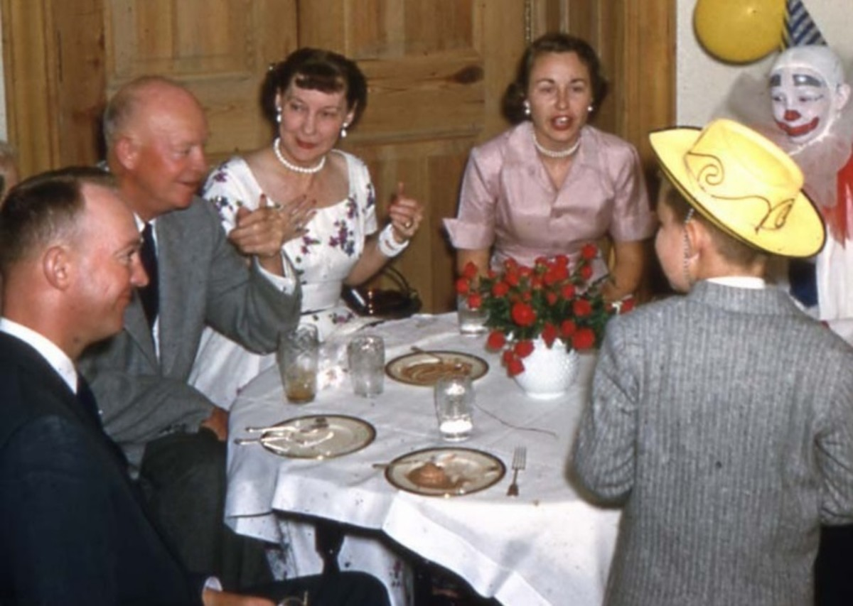 The Eisenhower family gathers for a birthday party. From left to right round the table: John Eisenhower, Dwight Eisenhower, Mamie Eisenhower, Barbara Eisenhower, unidentified clown, David Eisenhower with back to camera.