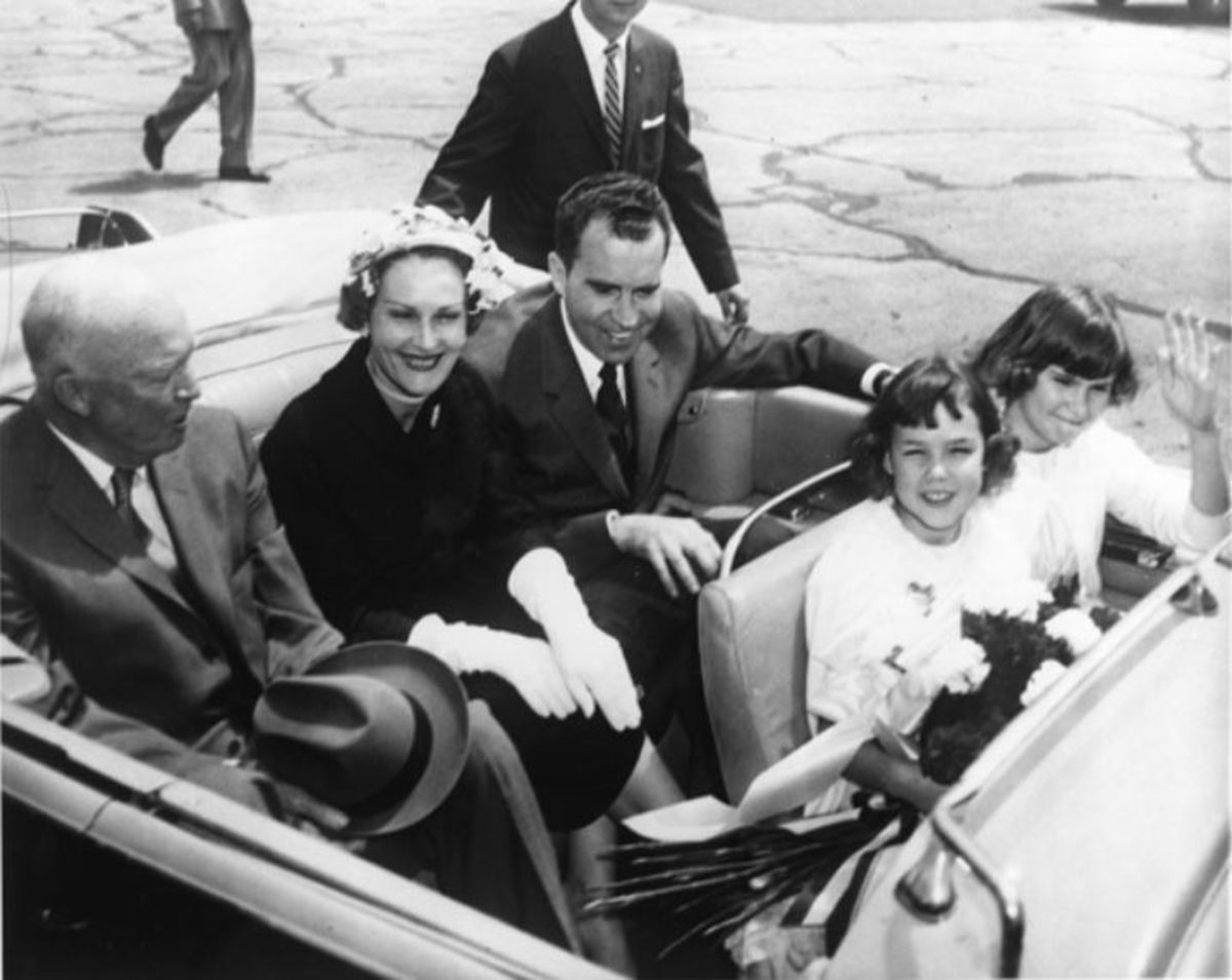 Vice President Richard Nixon rides in the back seat of an automobile with Dwight Eisenhower and Pat Nixon upon the Nixons' return from their 1958 goodwill tour of South America.
