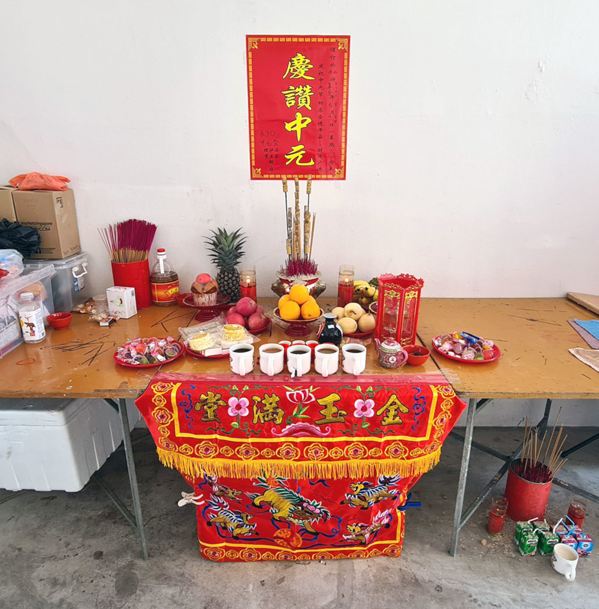 """A community altar during the Ghost Festival. The poster above the altar says """"celebrating Zhongyuan"""""""