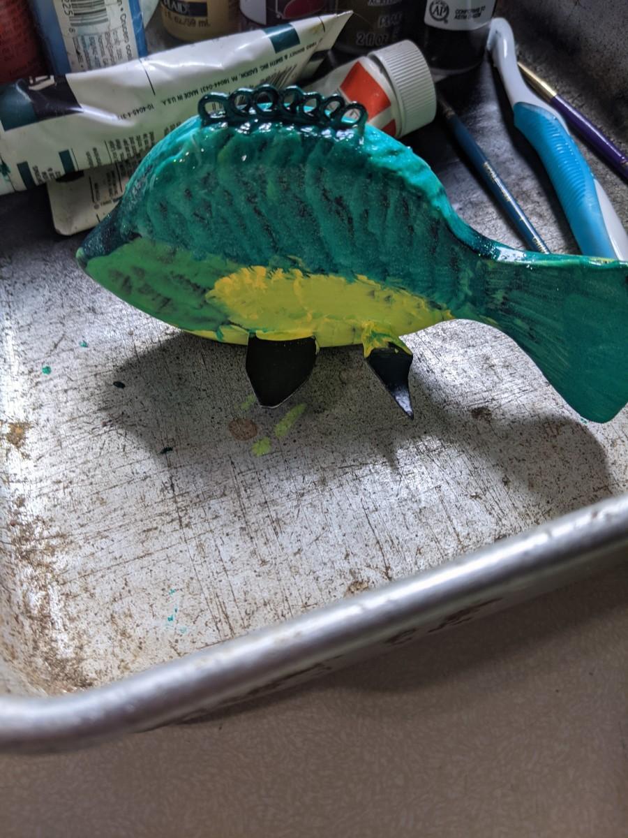 Dark green on top, yellow belly, light green gills, brush off paint for full spot and eye ball.