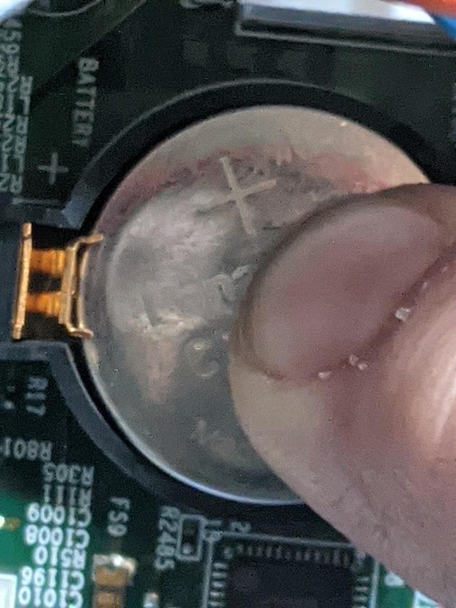 Slide under small clip then press down