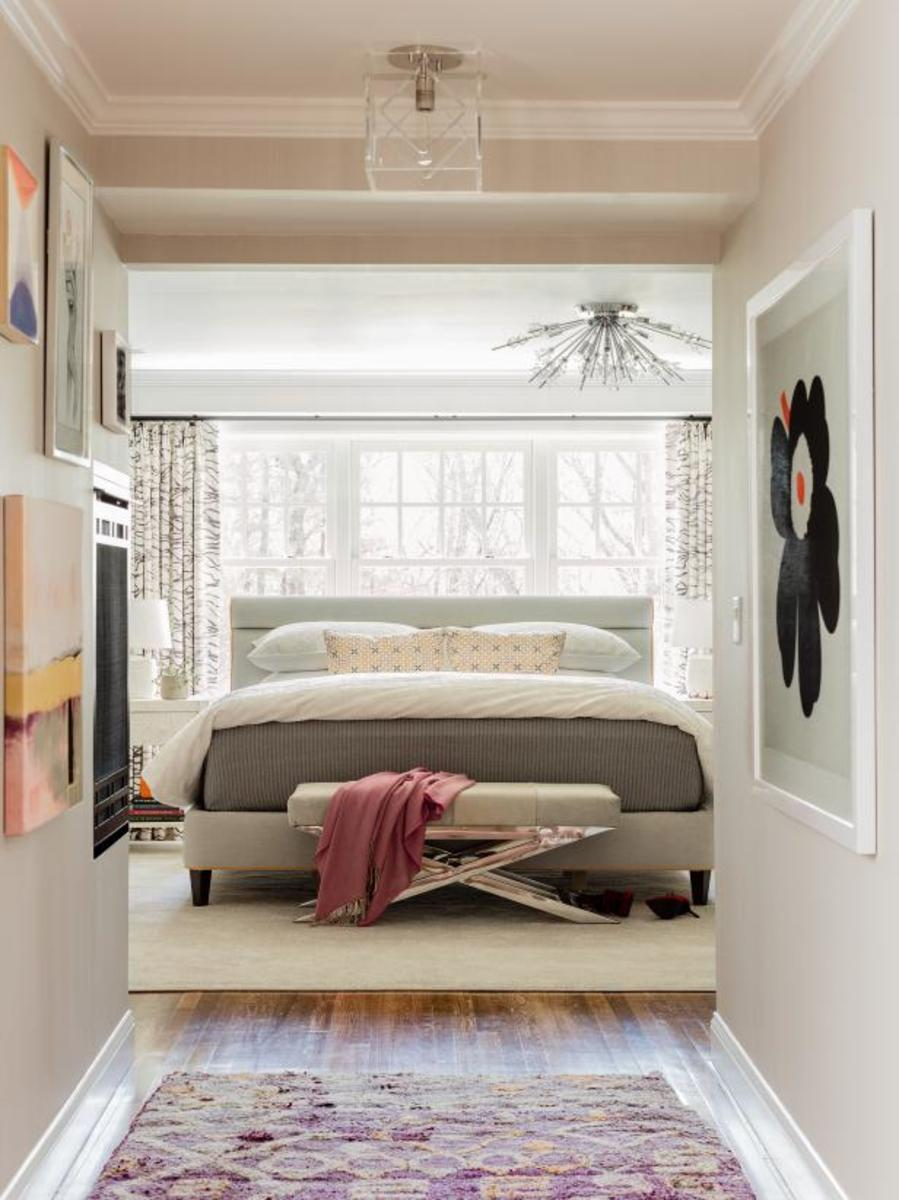 Abstract artwork lines the entry hallway walls and brings a subtle touch of color to the design.