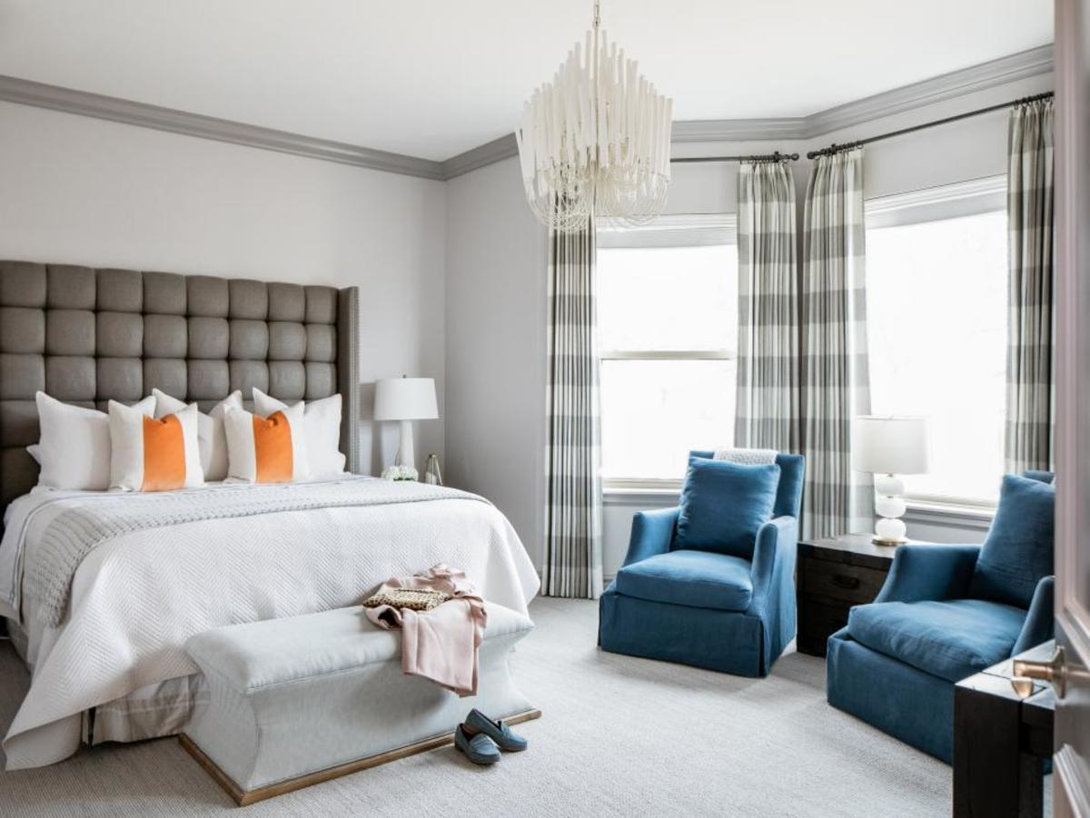 The plush of the headboard, gray wall, the blue velvet chairs and the light pendant.