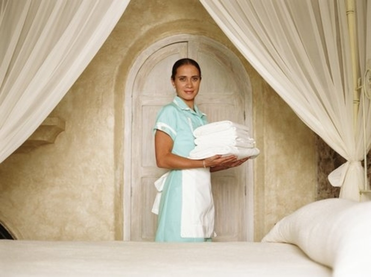 pretty girl dressed as a housekeeping attendant in full uniform with towels standing in front of a bed with an elaborate hotel door behind her