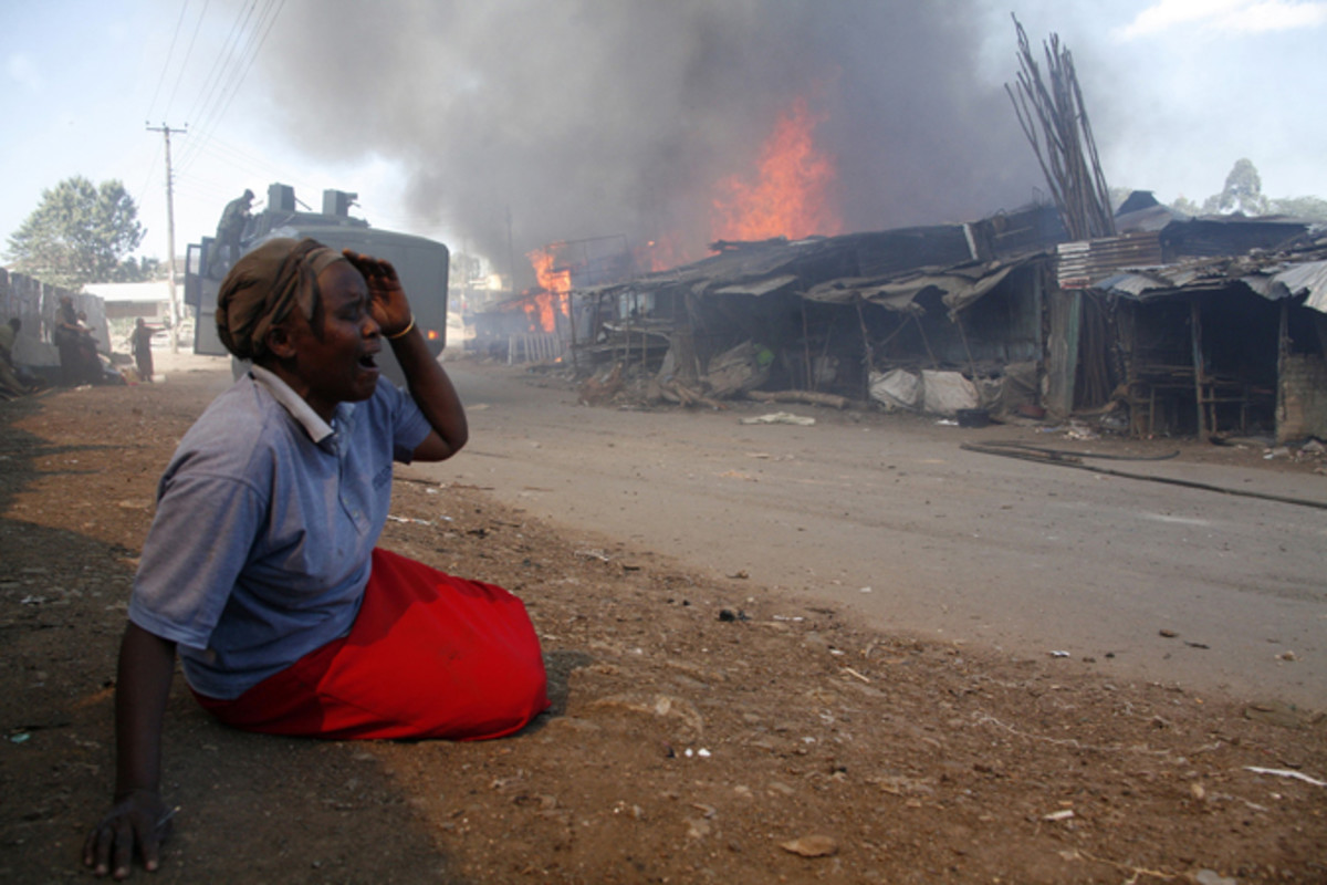 A woman cries after her house is burnt down after post election violence
