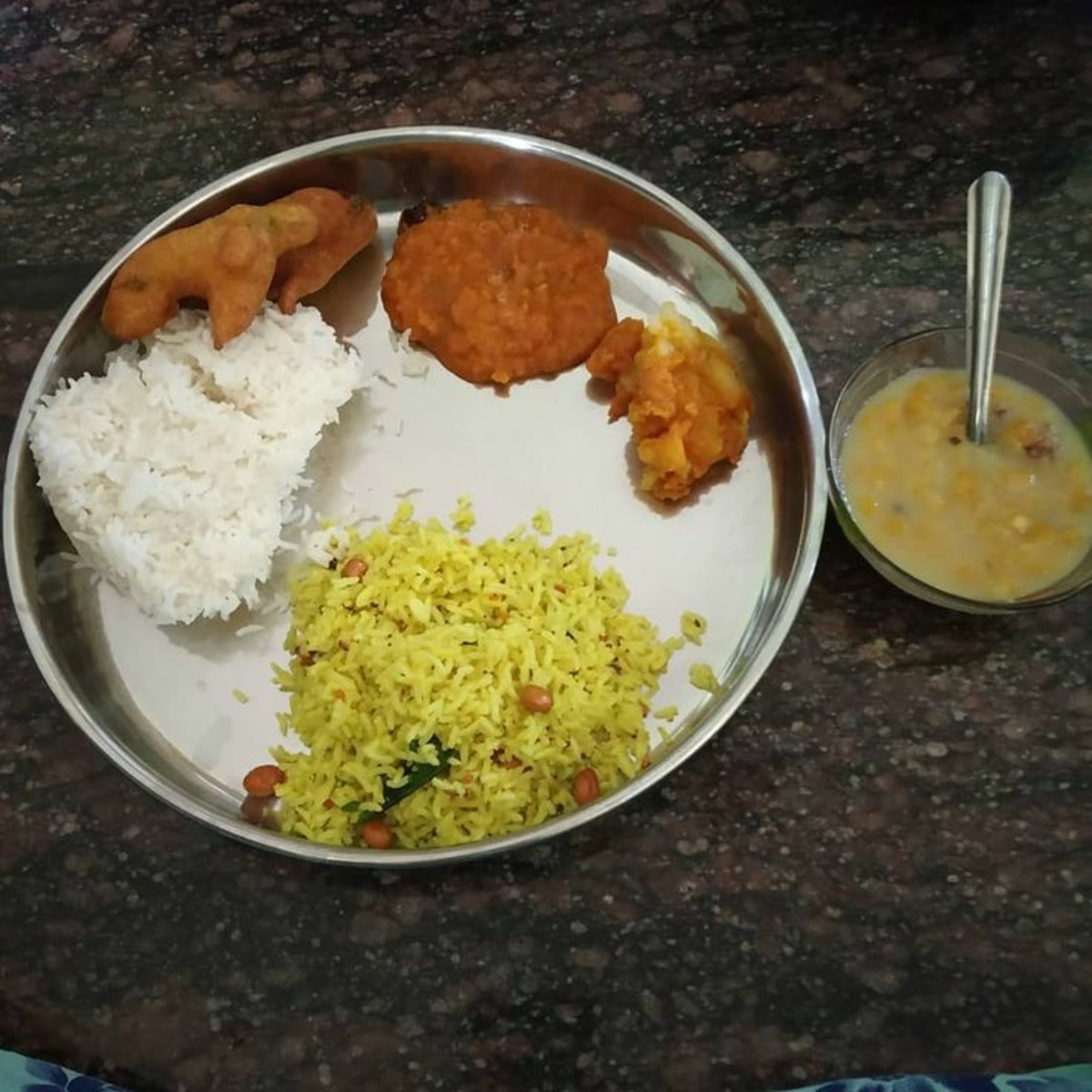 A typical Andhra thali including dal in fiery red.