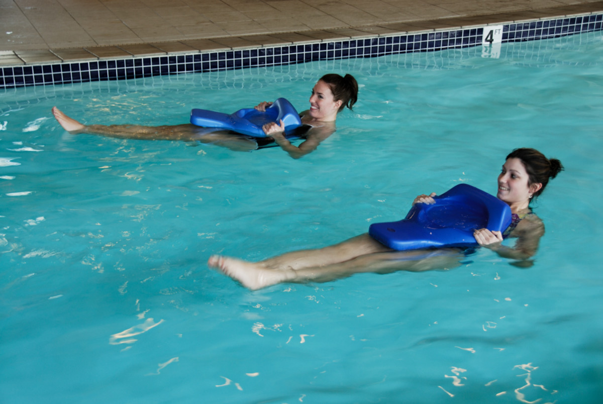 Two girls swimming with the swim board