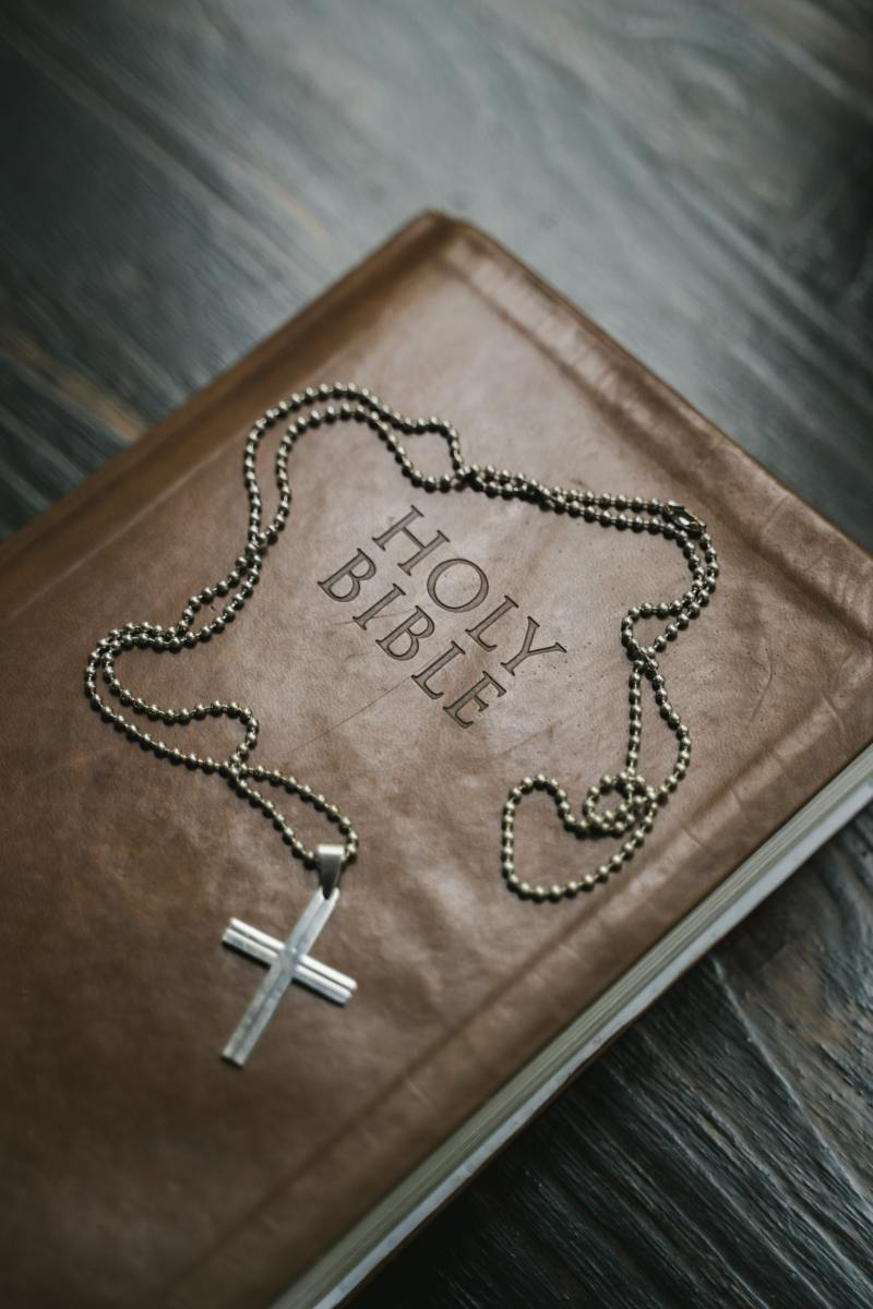 Silver cross pendant necklace on brown wooden table