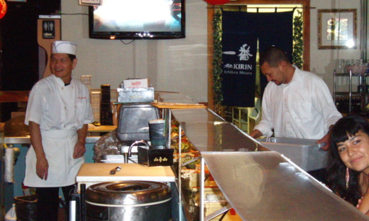 Taking a quick break, one of the cooks watches too. Note the glass counter above the boat run. This is where the cooks place special orders.