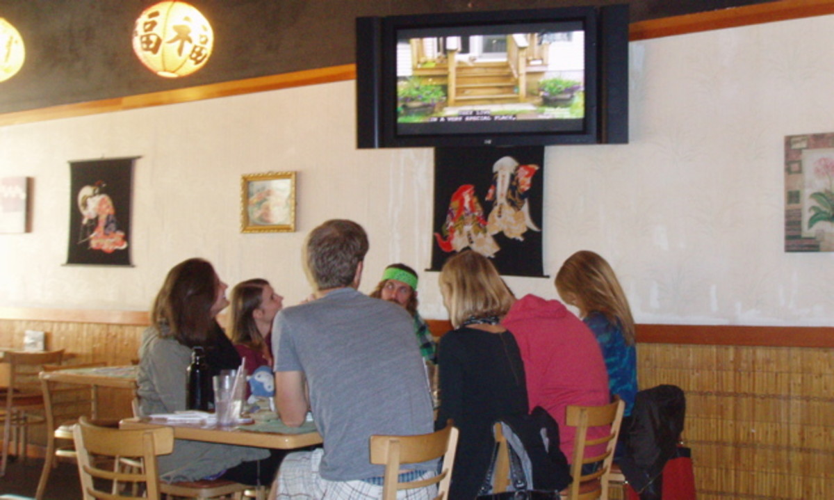 Restaurant table with patrons watching TV. Tables fill the front of the restaurant and run down the sides of both walls on either side of the sushi bar.