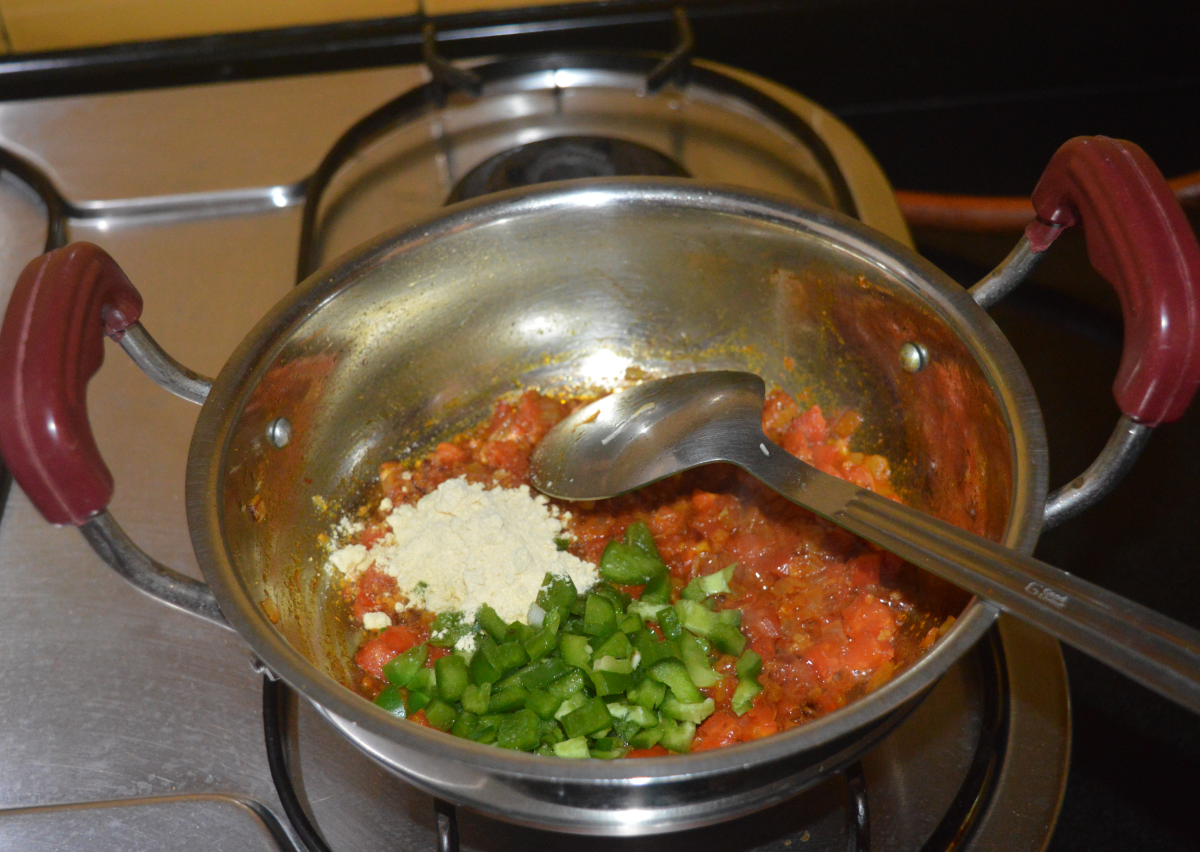 Step three: Add chopped capsicum and chickpea flour (besan). Mix well and saute for a minute.
