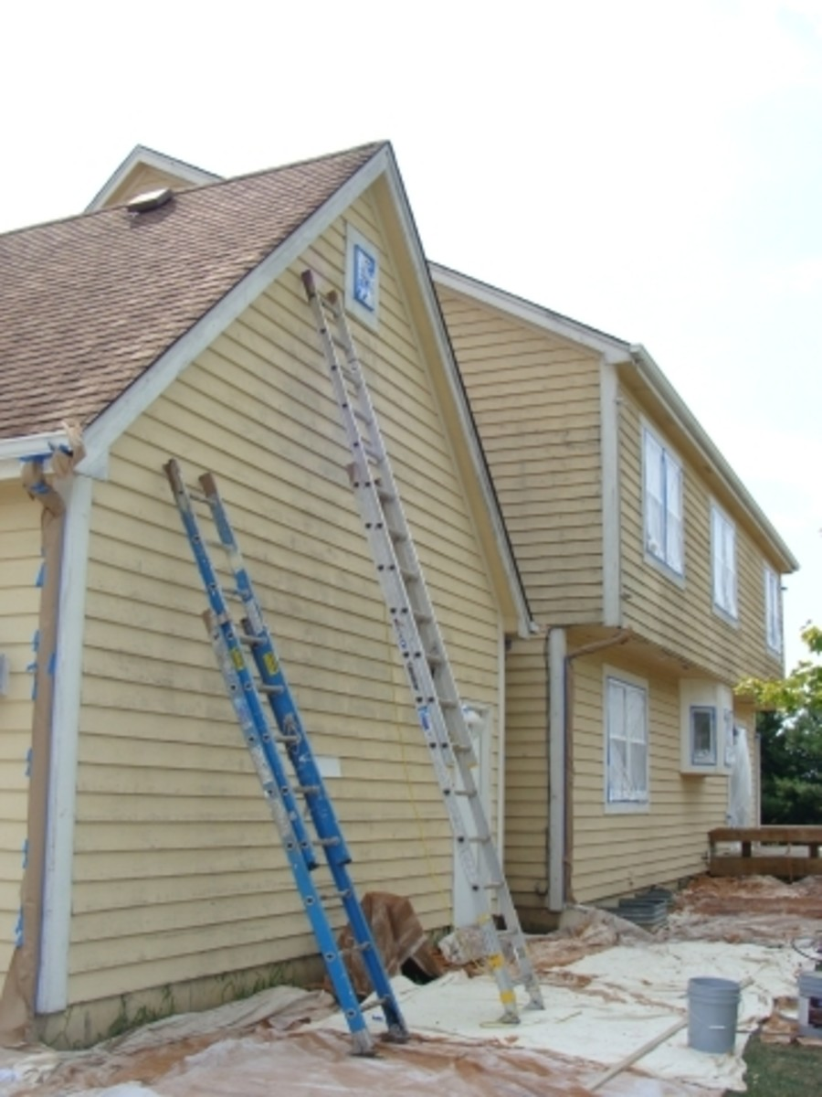 Preparing a cedar-sided house for stain.