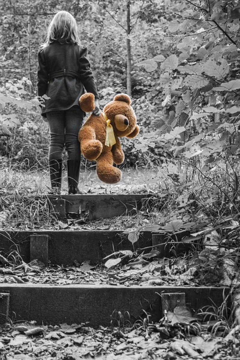 Carrying a teddy bear through the woods.