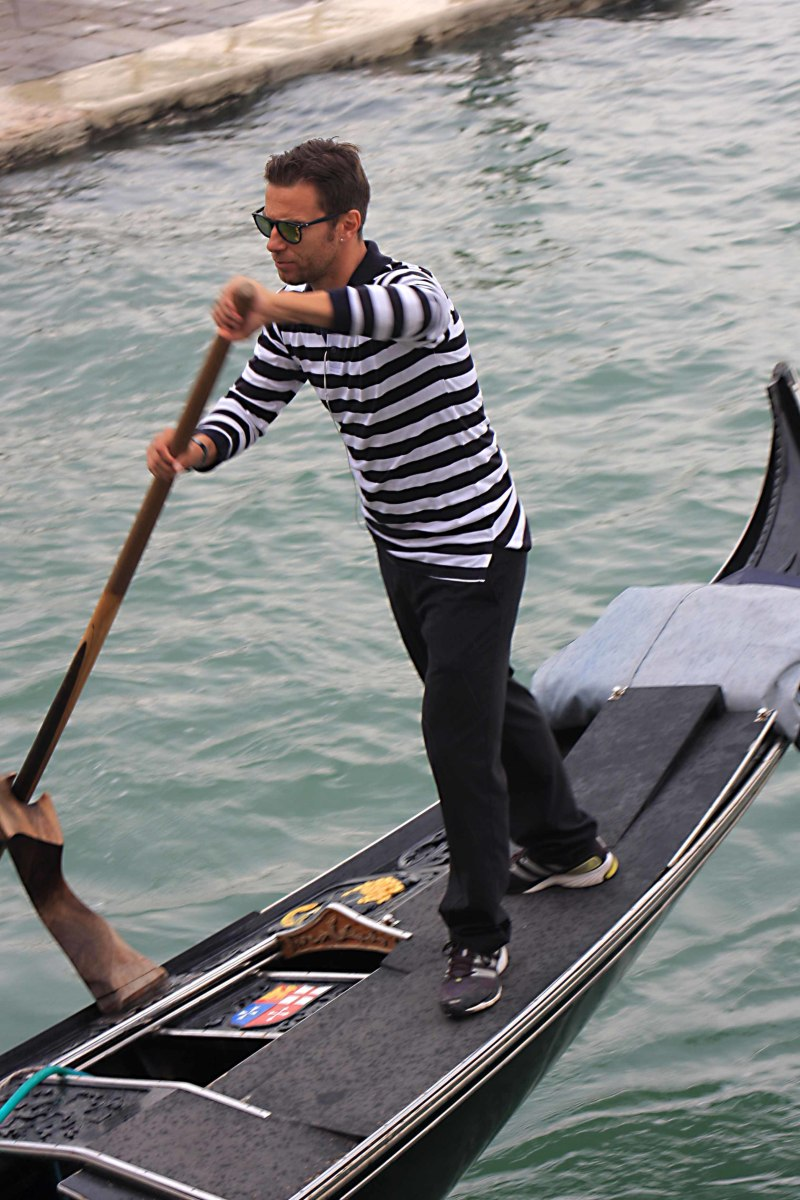 A gondolier plies his trade, navigating the canals of Venice just as his predecessors have done for hundreds of years
